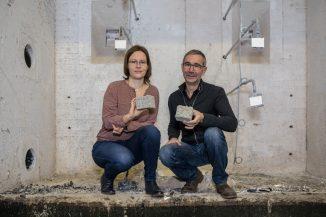 Empa-Know-how für die Industrie: Franziska Grüneberger und Willi Senn entwickelten ein neues Bindeverfahren, welches den Isofloc-Dämmstoff deutlich feuerfester macht als bisher. Hier stehen die beiden im Brandlabor, in dem die entscheidenden Versuche stattfanden. Bild: Empa