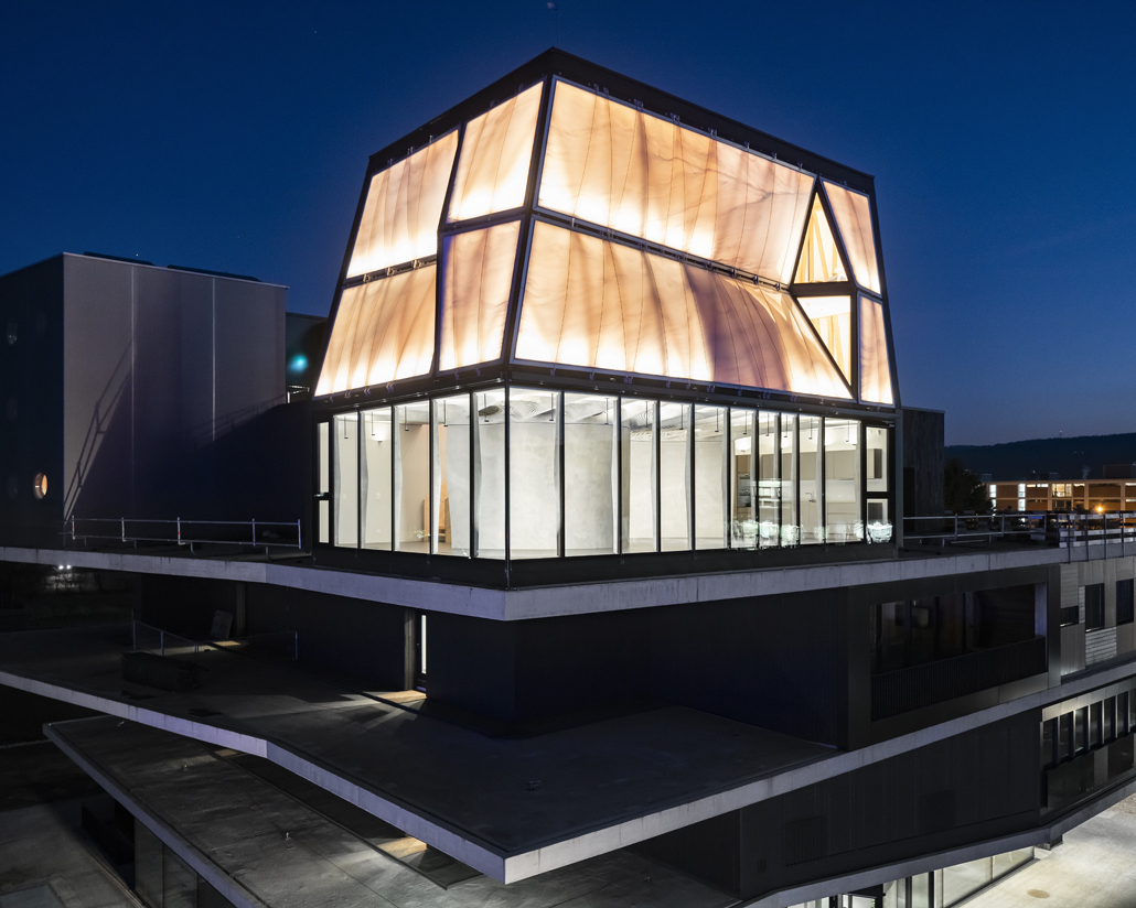 DFAB HOUSE und NEST leuchten in der Abenddämmerung. Foto: Roman Keller